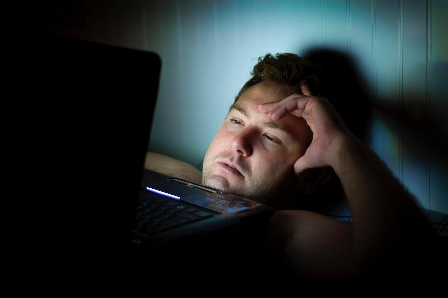 Un homme couché qui regarde un ordinateur - Précision Chiropratique