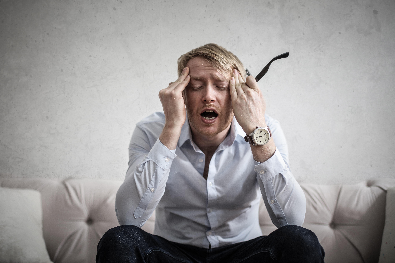 Un homme assis qui a mal àa la tête - Précision Chiropratique